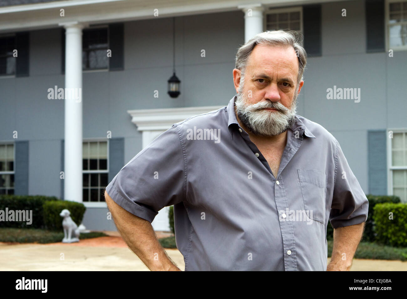 Unhappy homeowner poses in front of his two story columned southern home. - Stock Image