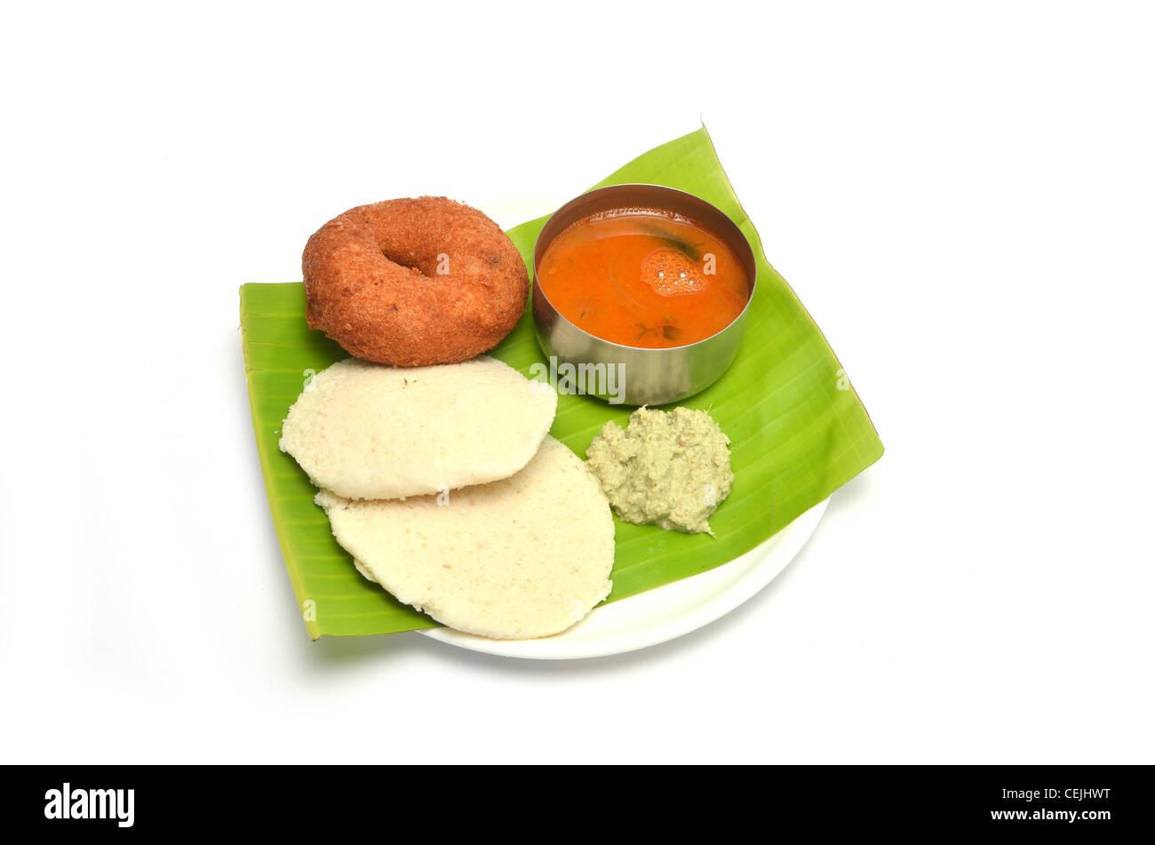 Idli, vada, sambar and chutney, south Indian breakfast served on banana leaf, isolated on white background Stock Photo