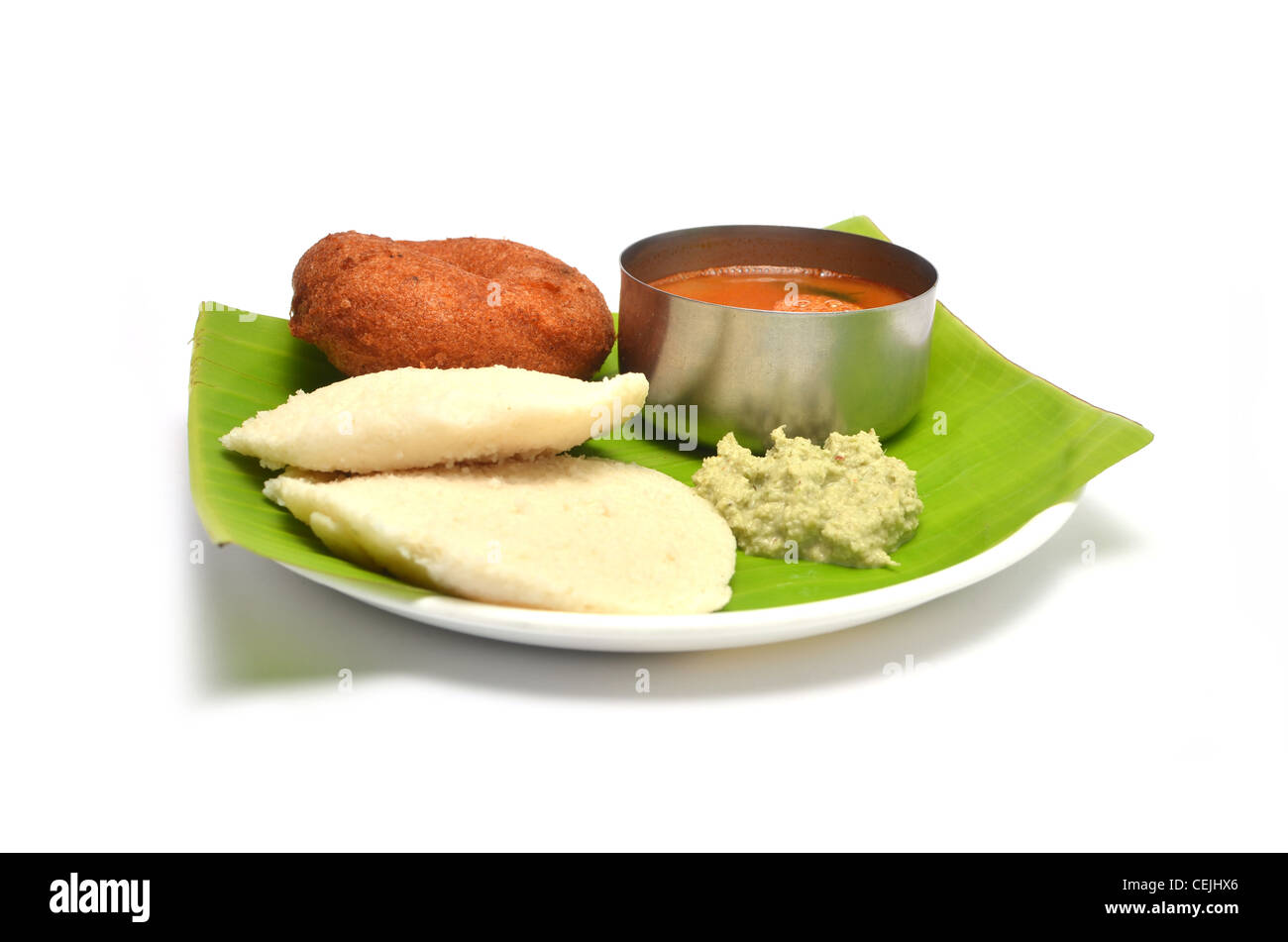 Idli, vada sambhar and chutney, south Indian dish served on Banana Leaf, isolated on white background Stock Photo