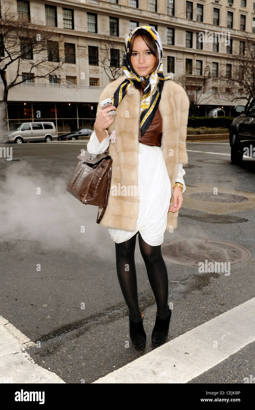 New York Street Style A female wearing thick black tights, a pale cream fur coat, white long sleeved gathered dress, - Stock Image