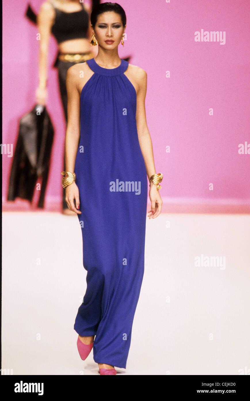 8e4e730bca6 Yves Saint Laurent Spring Summer Model wearing long dark blue halterneck  dress, accessorized with gold bracelets