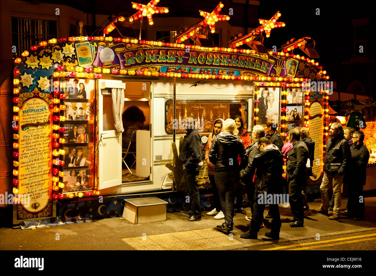 A small crowd waiting for their fortune to be told by a Romany gypsy fortune teller. Goose Fair, Nottingham, England, - Stock Image