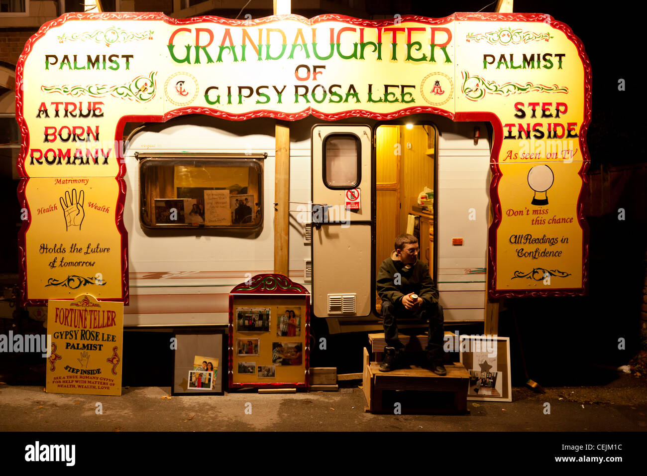 A boy sits on the steps of fortune teller's caravan at Goose Fair in Nottingham, England, UK - Stock Image