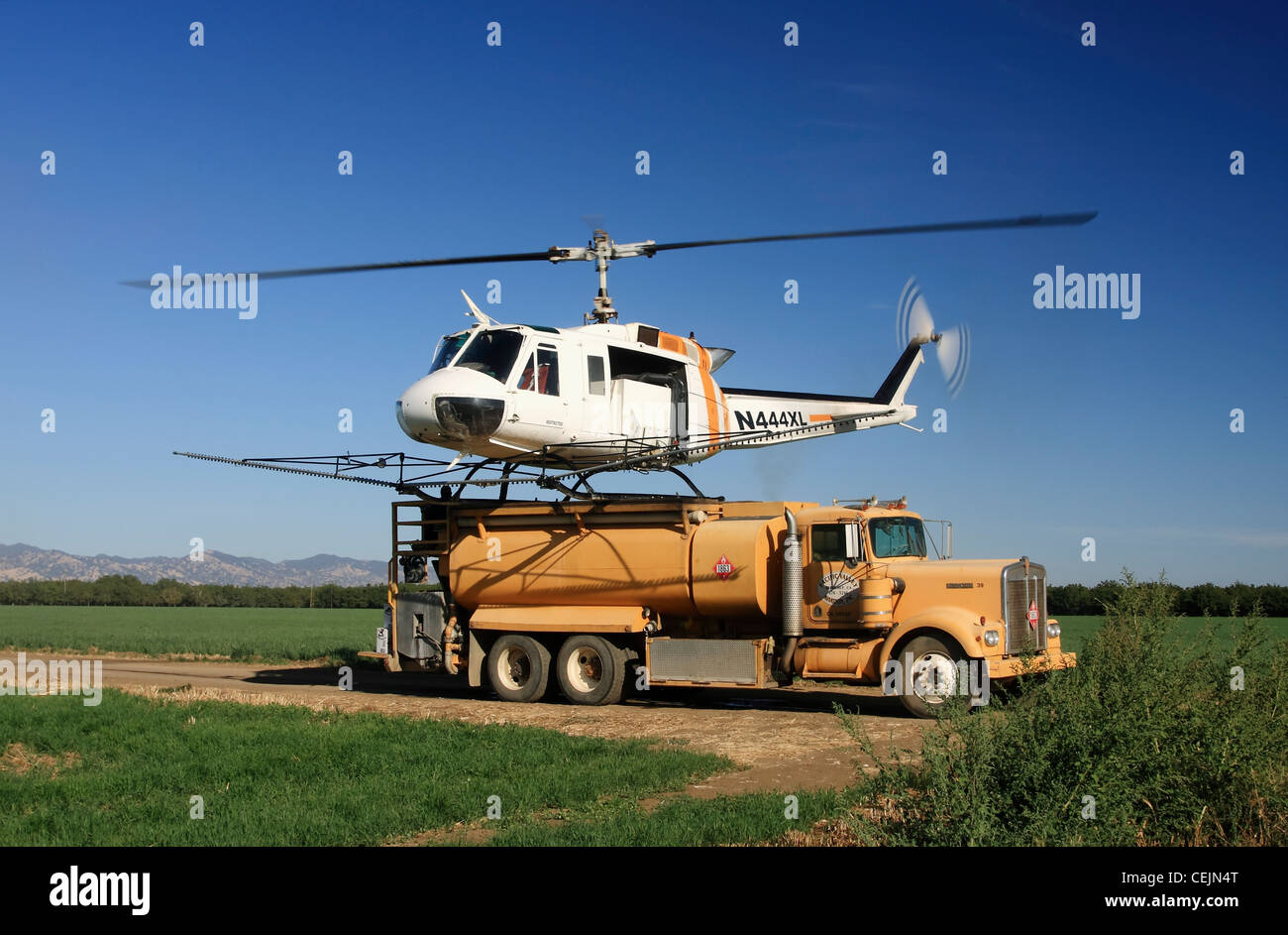 Helicopter crop duster lands on the back of a chemical truck to refill the tanks during spraying operations of a - Stock Image