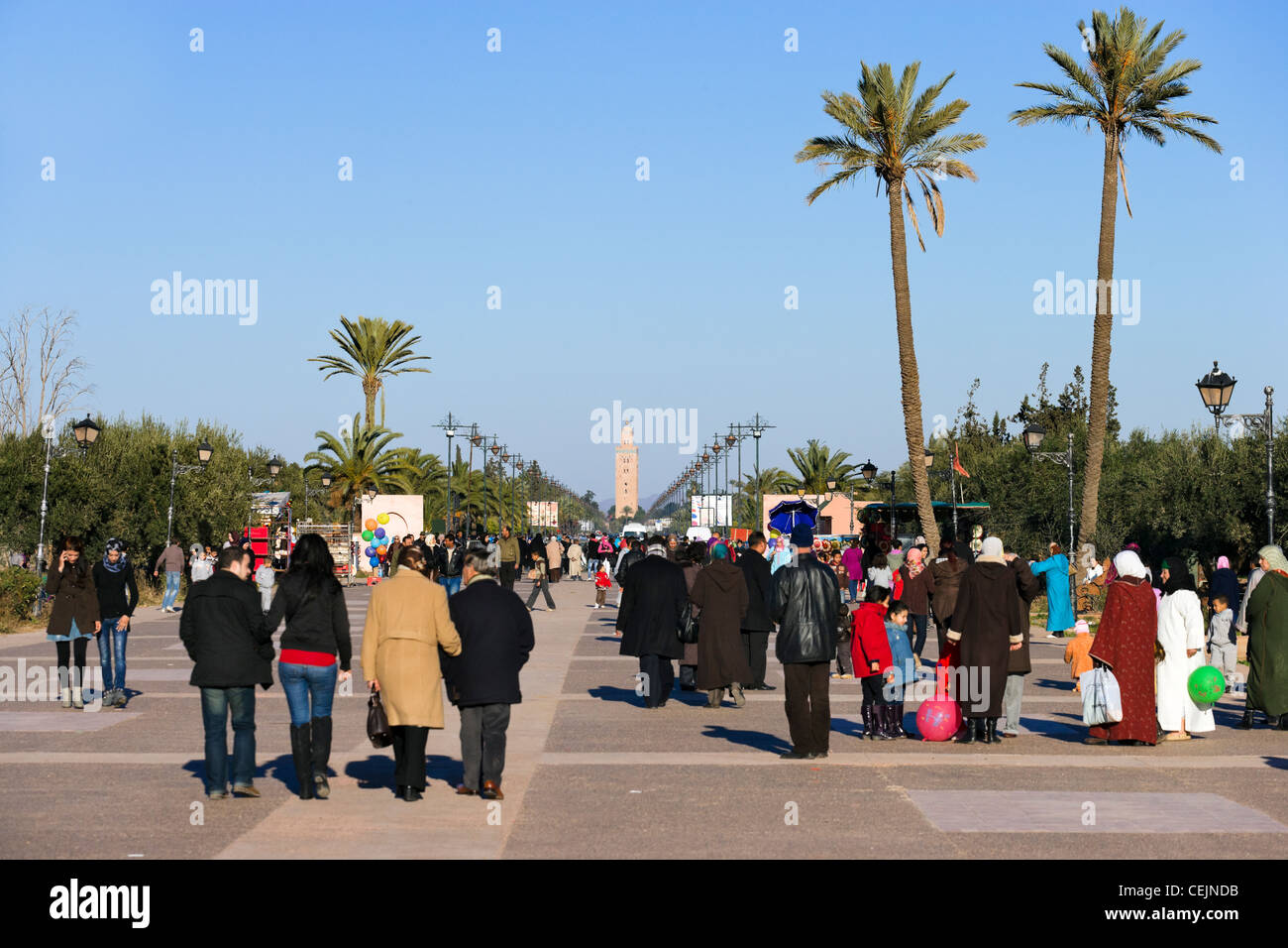 Local people in the Menara Gardens with the minaret of the Koutoubia Mosque in the distance, Marrakech, Morocco, - Stock Image