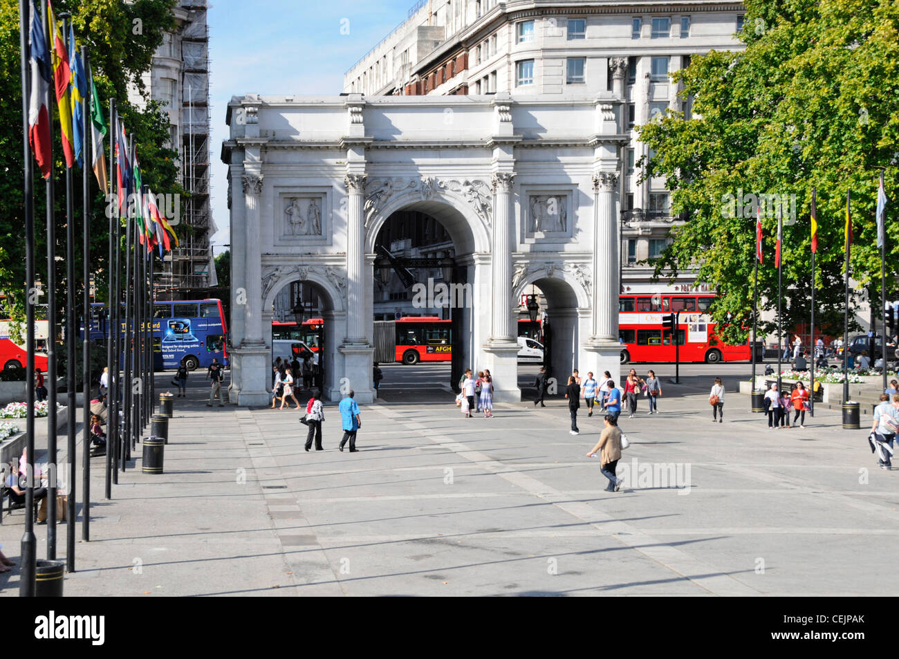 Tourists at Marble Arch19th century white marble faced triumphal arch in middle of major road traffic roundabout - Stock Image