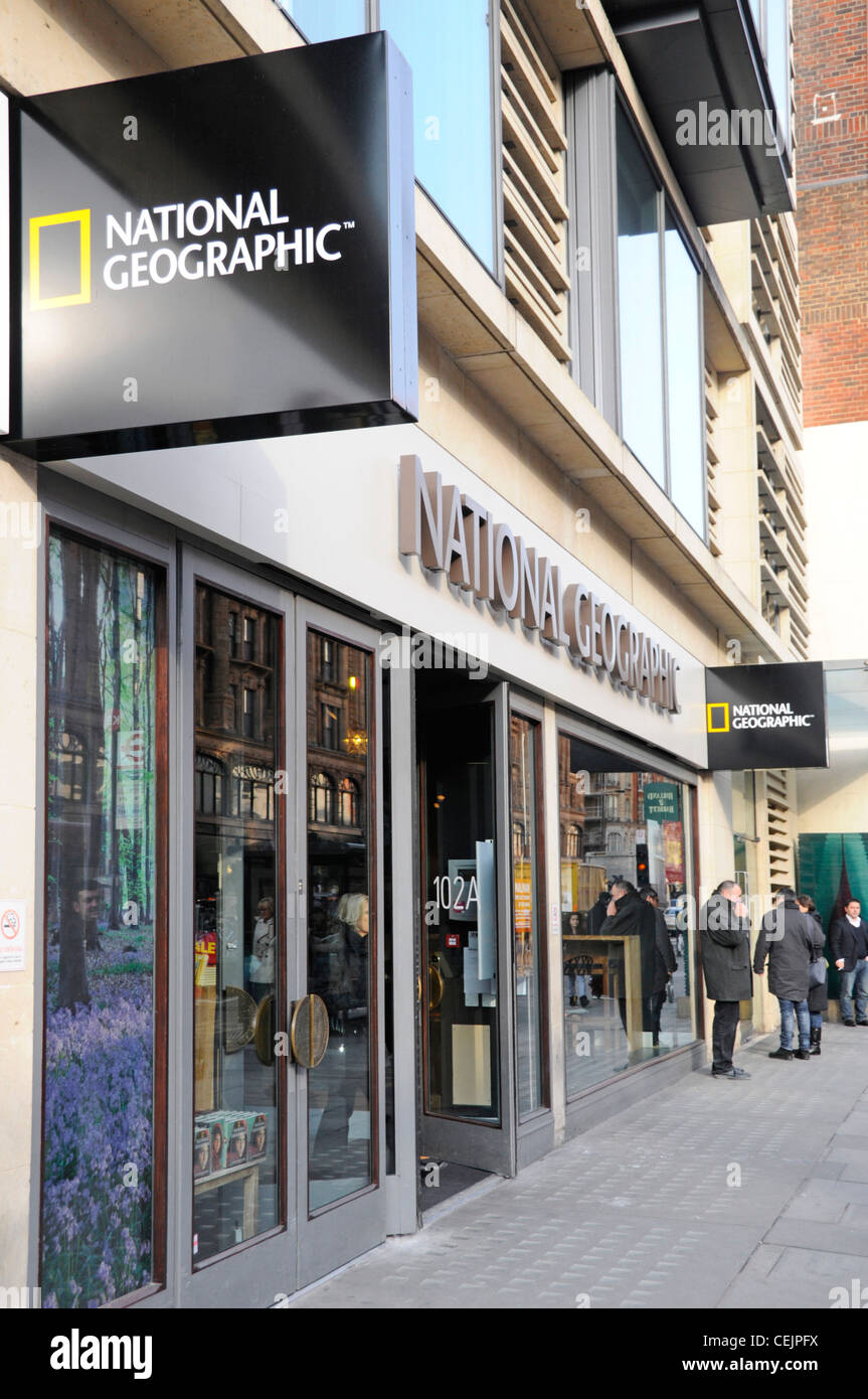 Pavement street scene with National Geographic shop front and signs Brompton Road Kensington London England UK - Stock Image