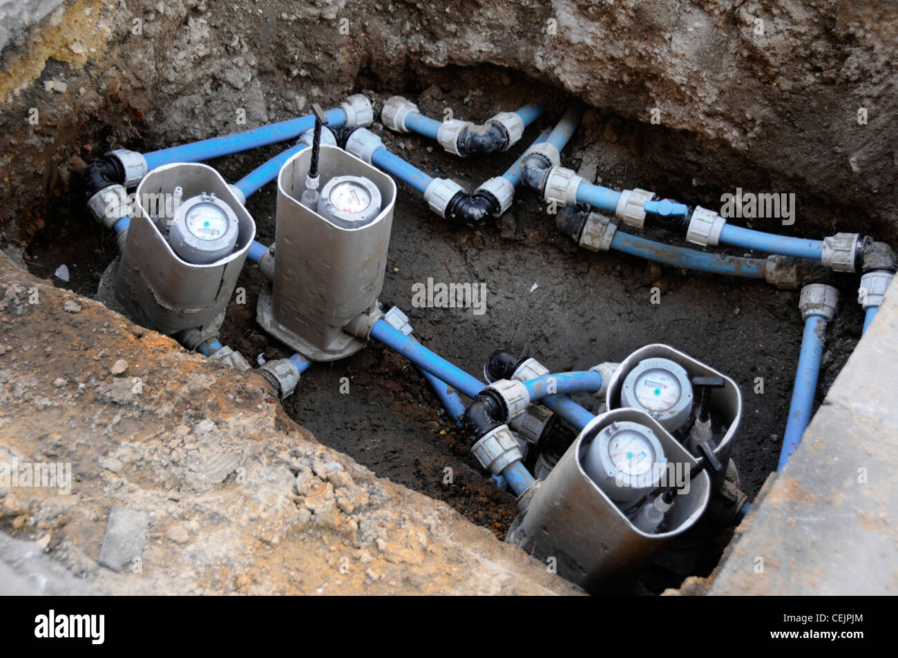 Water meter renewal in pavement pit part of water utilities infrastructure replacement of old iron pipe with plastic - Stock Image