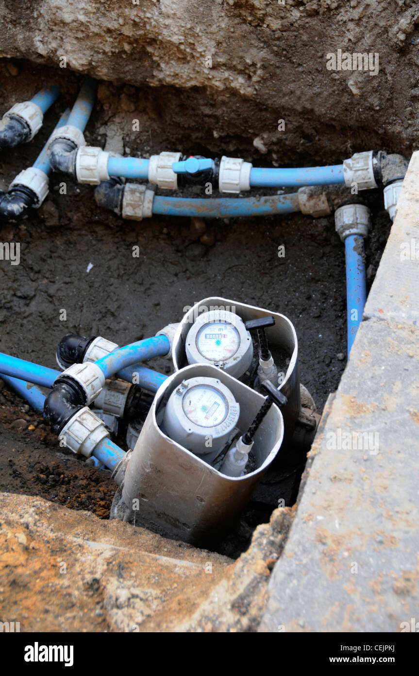 Water meters in pavement pit as part of upgrading work to replace corroding cast iron mains - Stock Image
