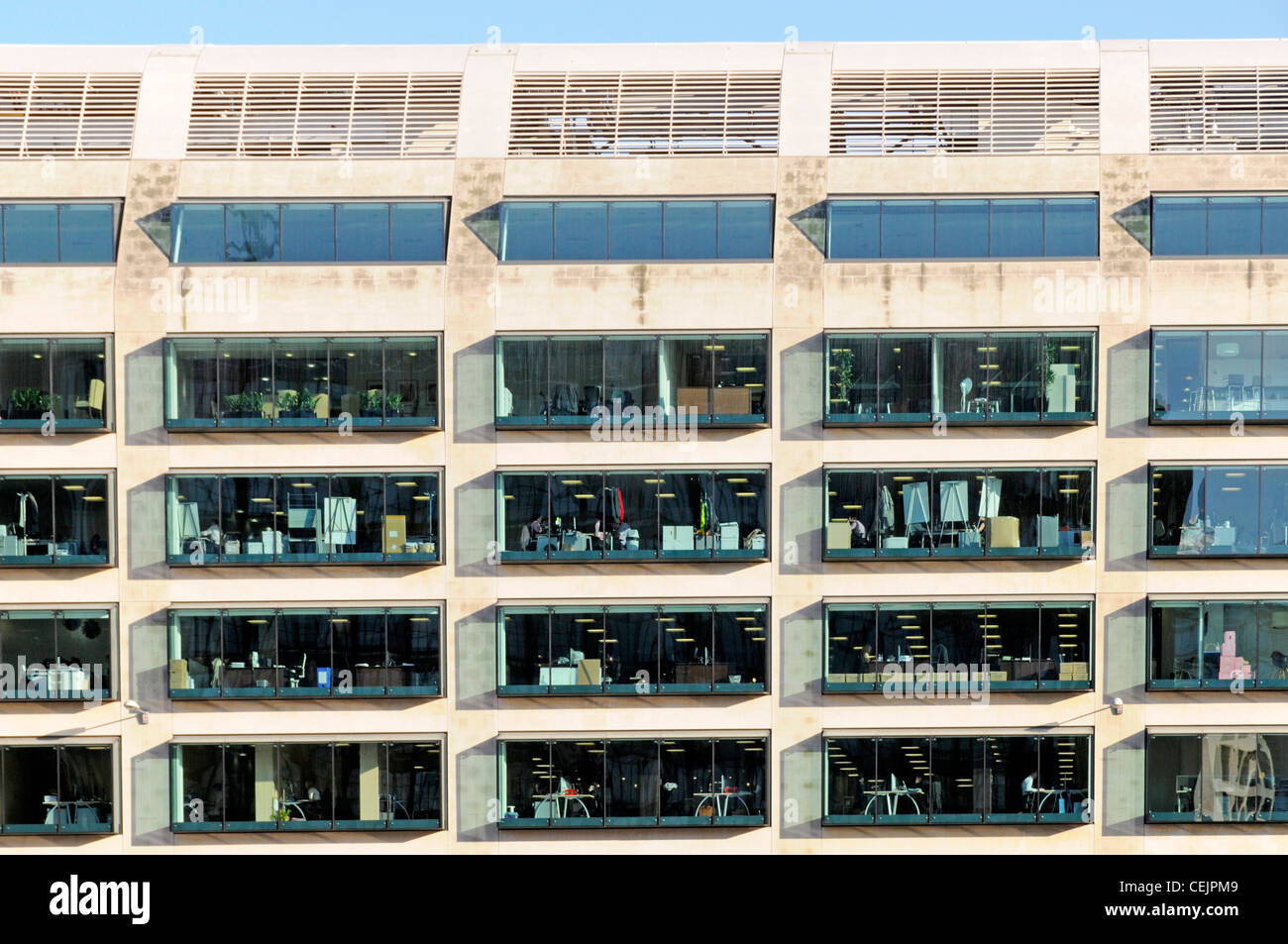 Office block view through windows from outside  in daylight with interior lights on City of London England UK - Stock Image