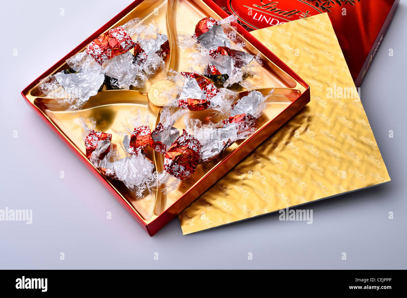 Empty box of Lindor Lindt milk chocolate truffles with only wrappers remaining - Stock Image