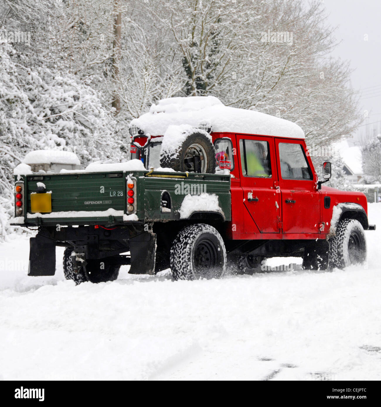 Snow scene Land Rover Defender 130 4x4 driving on narrow country lane road in winter snowfall cold weather Brentwood - Stock Image