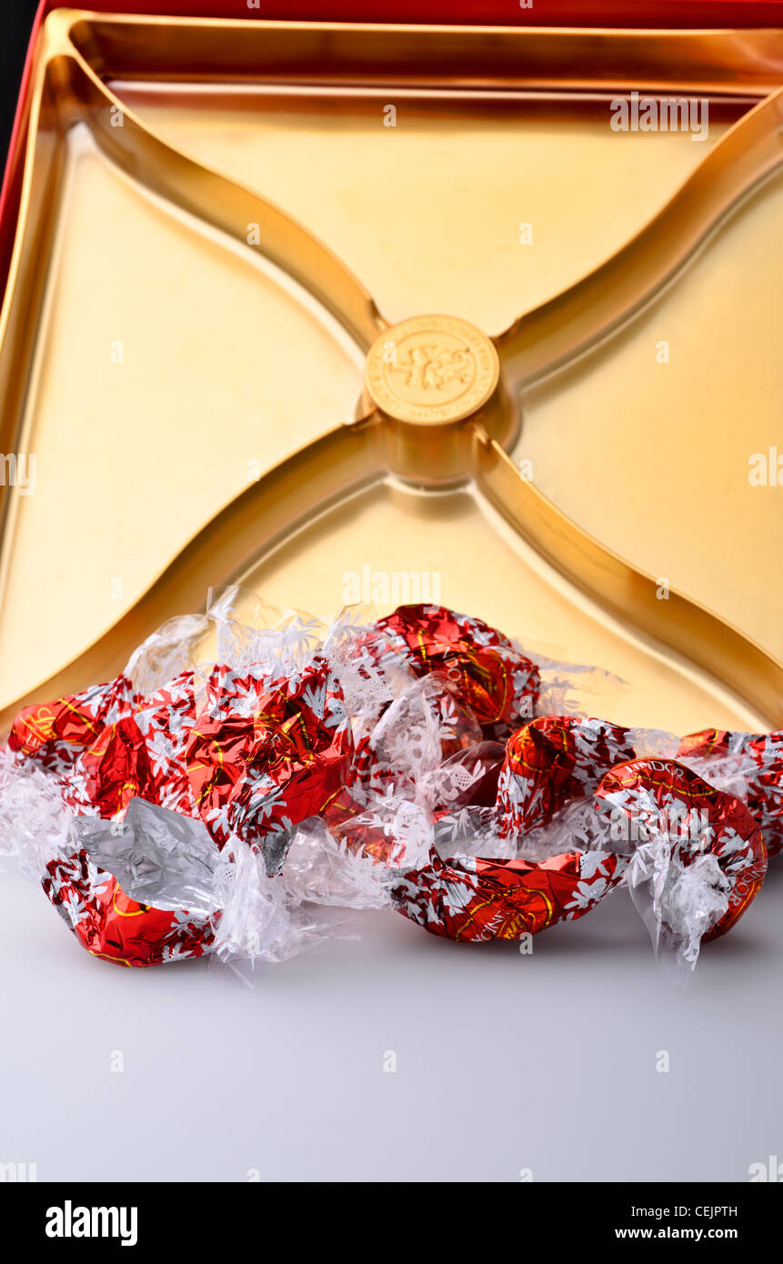 Remaining wrappers and empty box of Lindor Lindt milk chocolate truffles - Stock Image