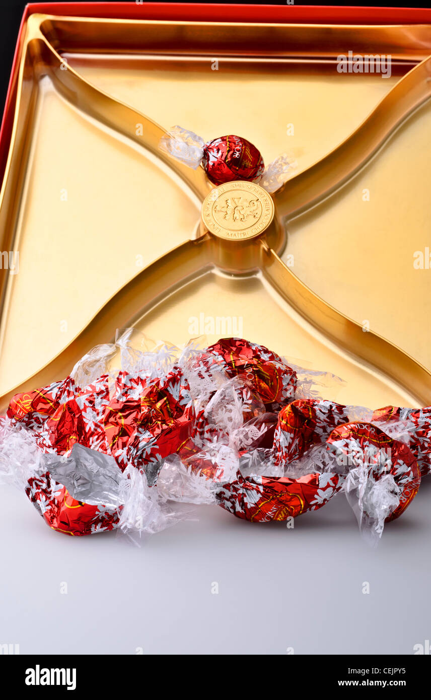 Last one Lindor Lindt milk chocolate truffles, empty wrappers in the box - Stock Image