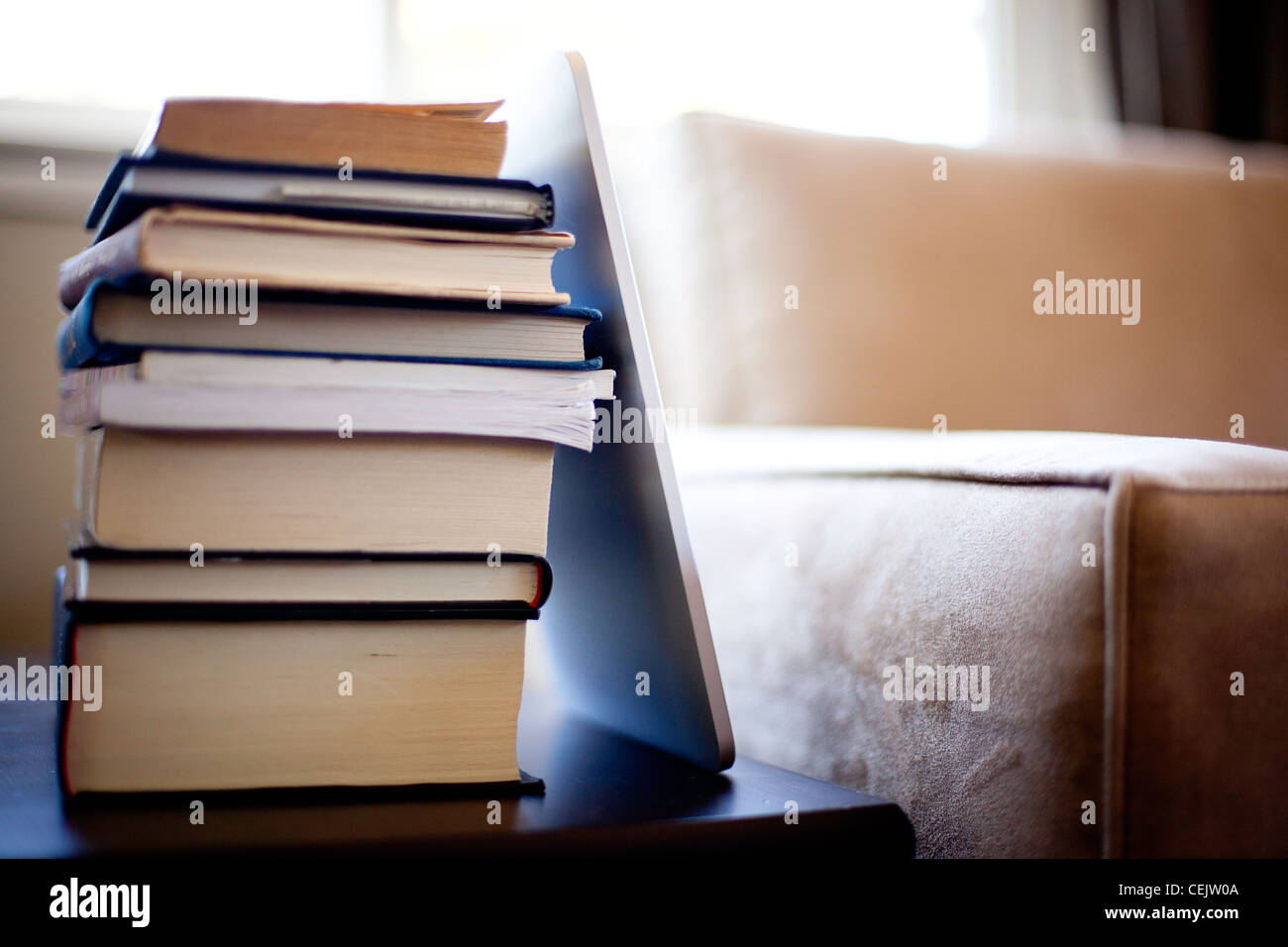 Stack of books by couch and Ipad - Stock Image