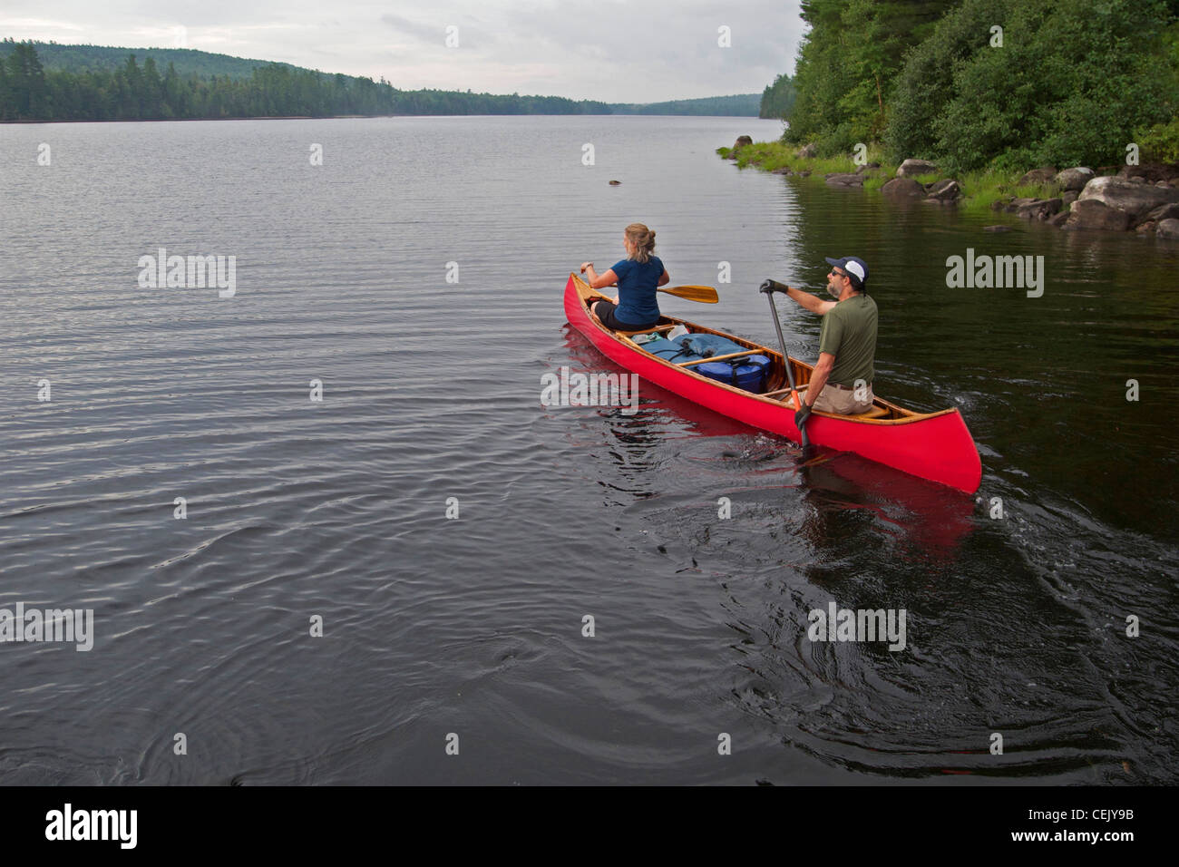 Couple in antique canoe paddle near the shore on Richardson Lake in western Maine. - Stock Image