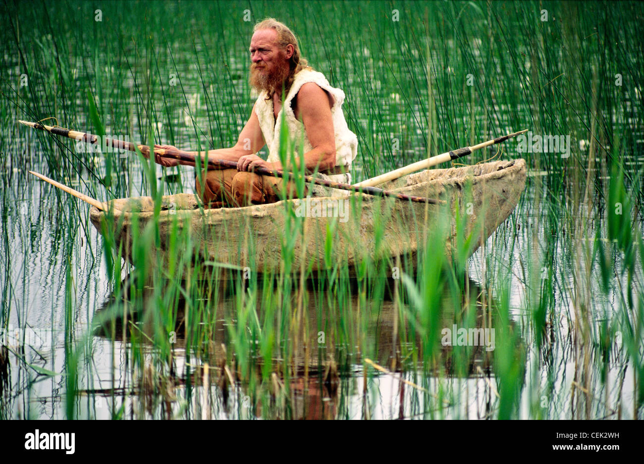 Neolithic re-enactment. Stone Age man holding fish spear in animal hide coracle boat on reed shore lake. Kilmartin, - Stock Image