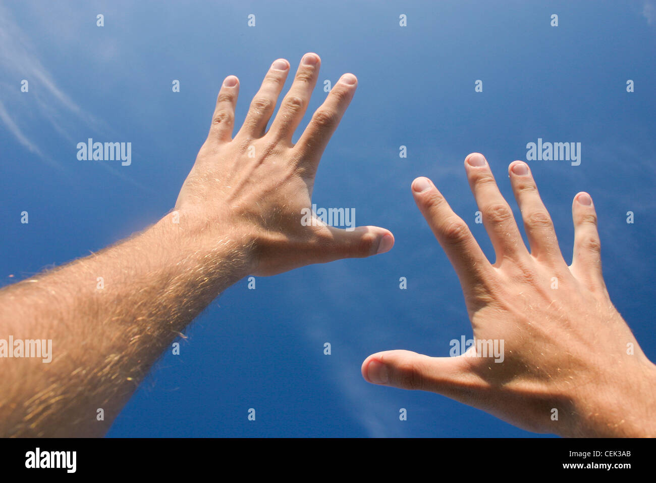 Two male hands stretching to reach the sky - Stock Image