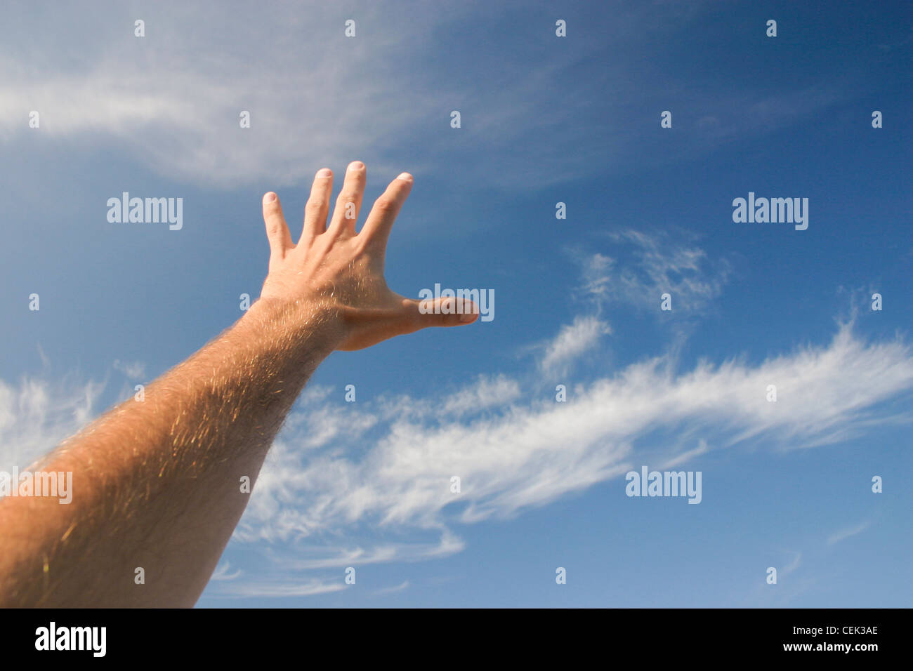 A male hand stretching to reach the sky - Stock Image