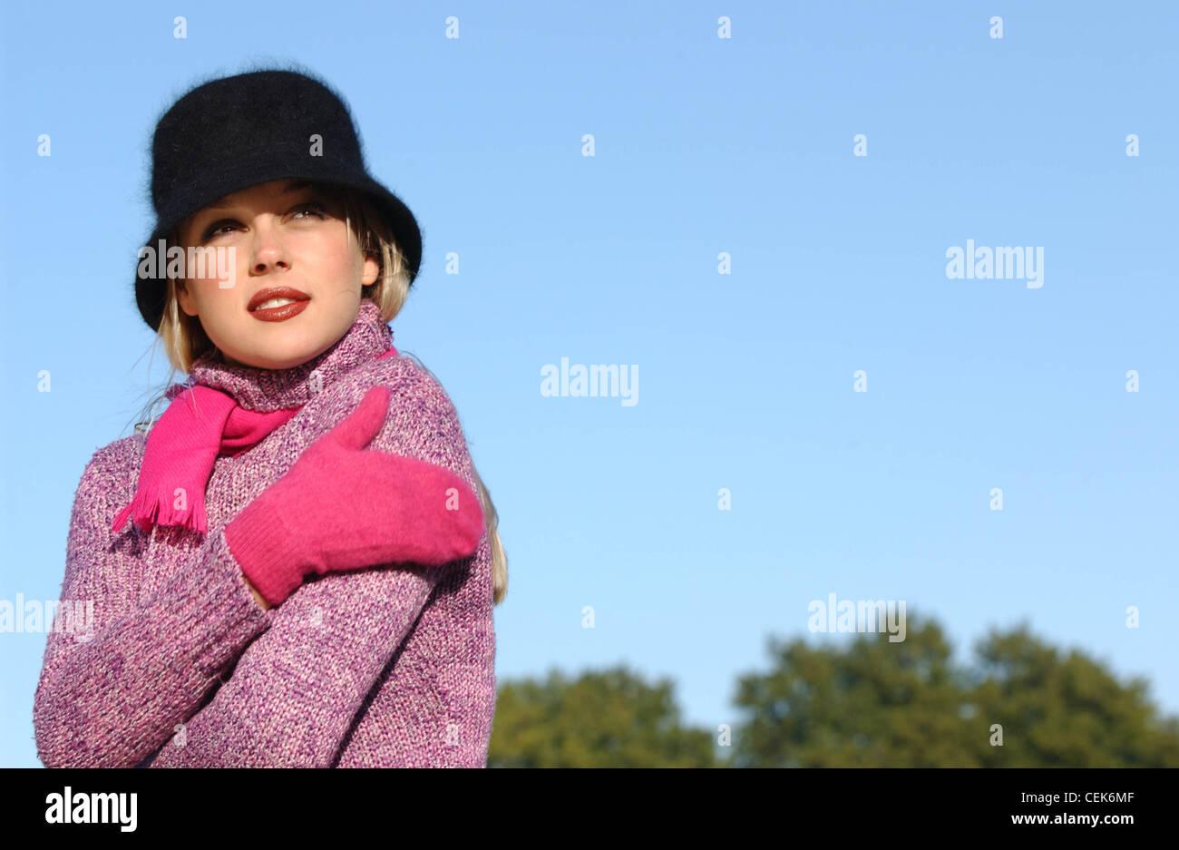 Female long blonde hair brown tones of make up wearing black angora hat purple roll neck jumper bright pink scarf - Stock Image