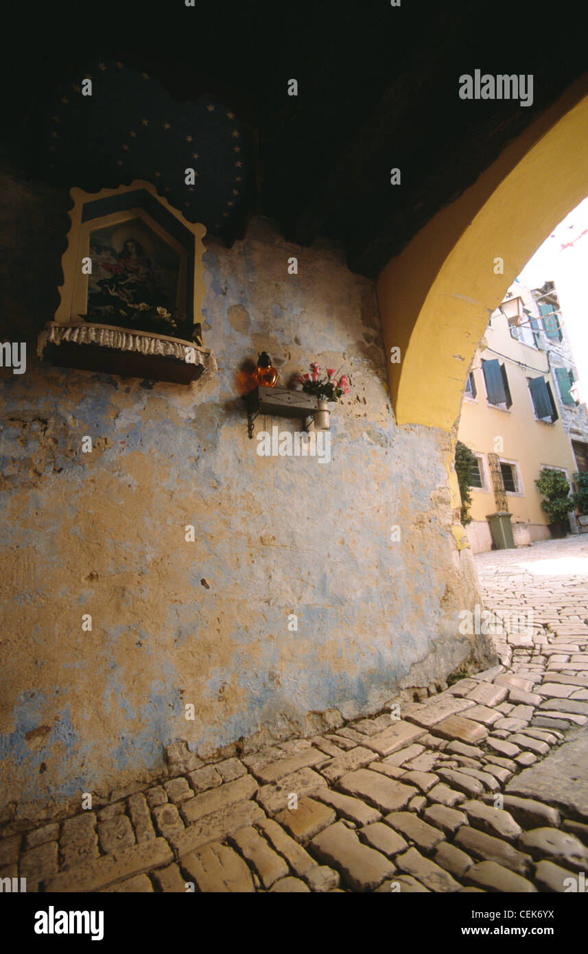 Christian iconography, candlelight and flowers of a public altar fixed at a wall in Rovinj, Istria, Croatia - Stock Image