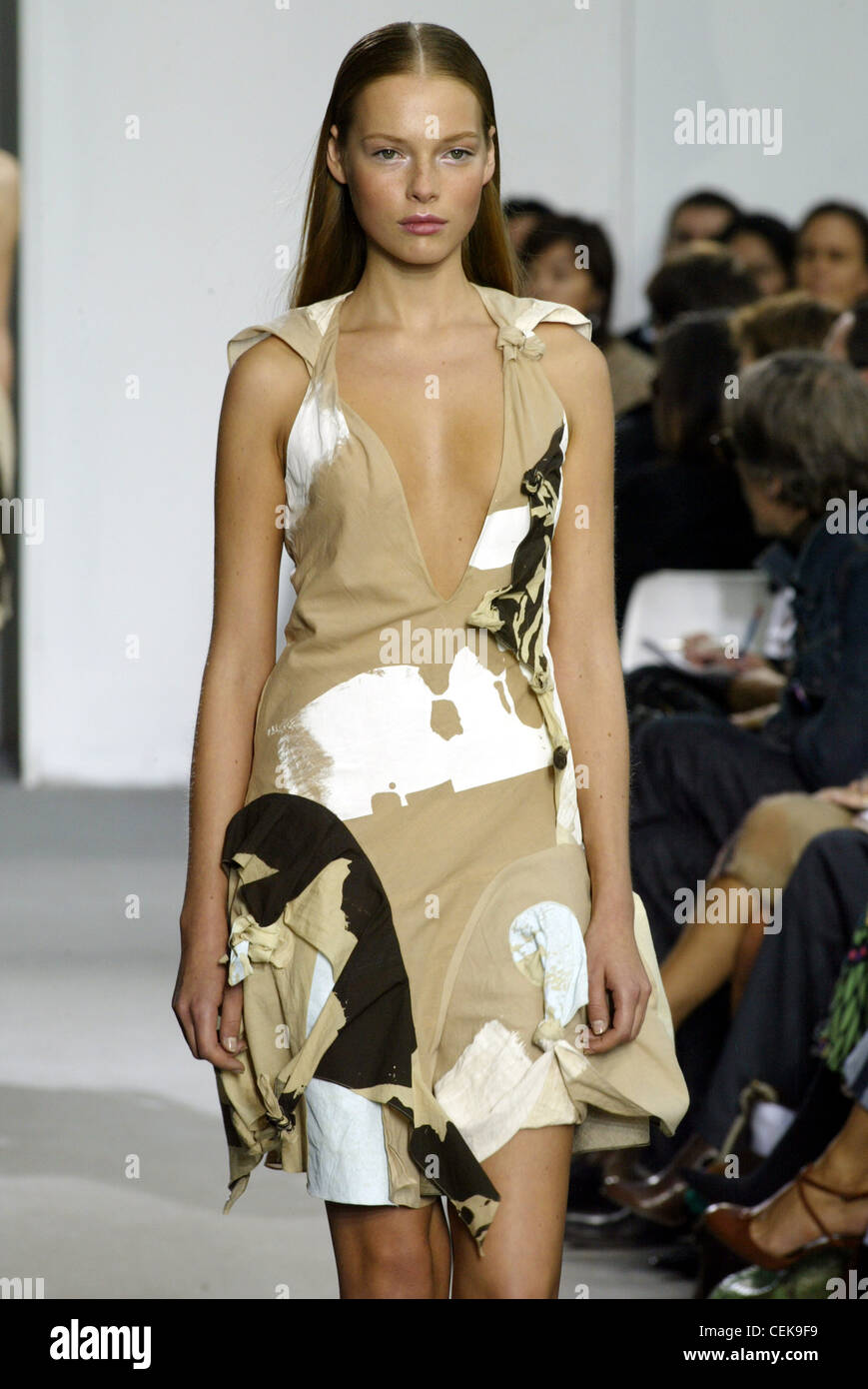 Helmut Lang Paris Ready to Wear Spring Summer Model long brunette hair tucked behind ears wearing biege white and - Stock Image
