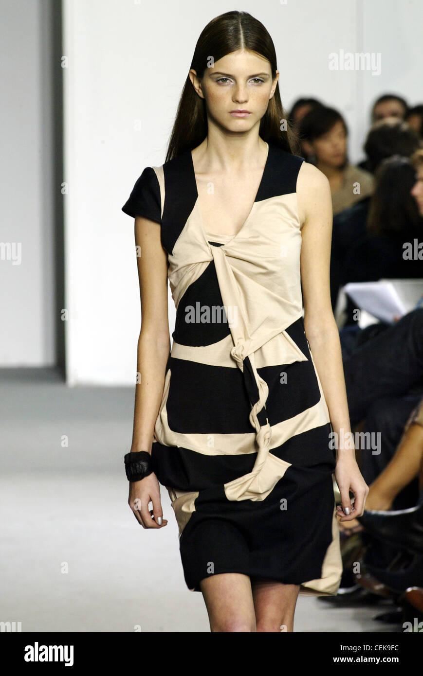 Helmut Lang Paris Ready to Wear Spring Summer Model long brunette hair tucked behind ears wearing black and beige - Stock Image