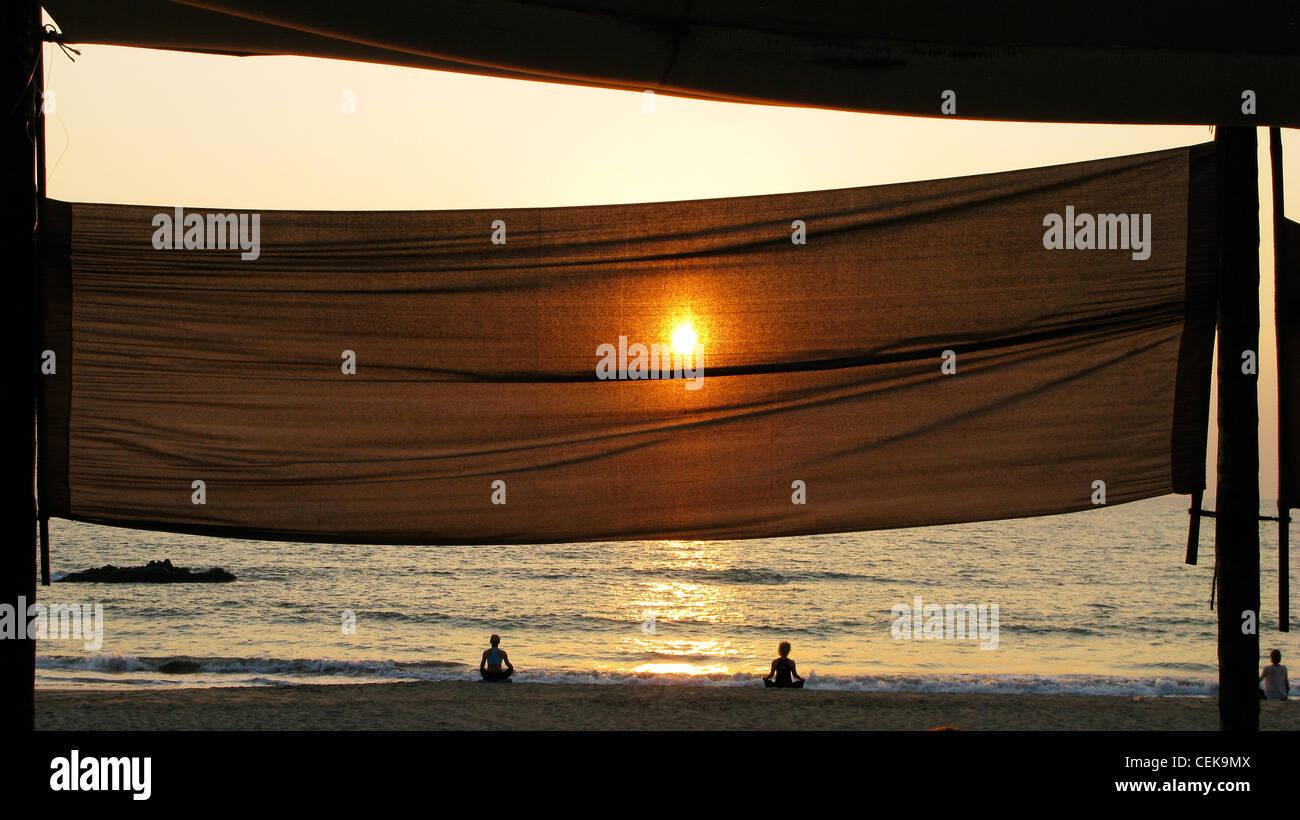 Sunset yoga and meditation on Patnem Beach, Goa (by Palolem beach), India - Stock Image