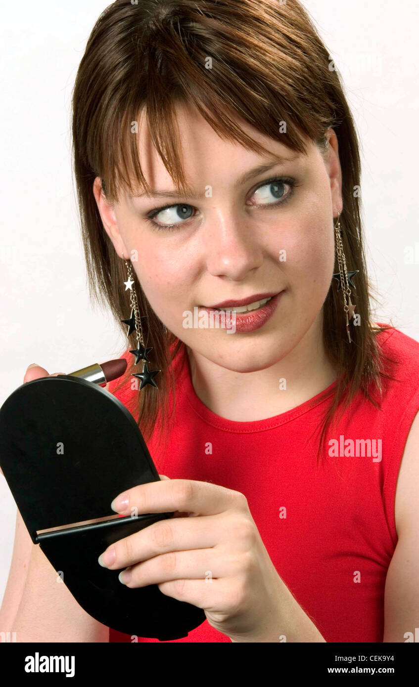 Female shoulder length brunette hair wearing long earrings silver stars and red sleeveless top, holding black compact - Stock Image