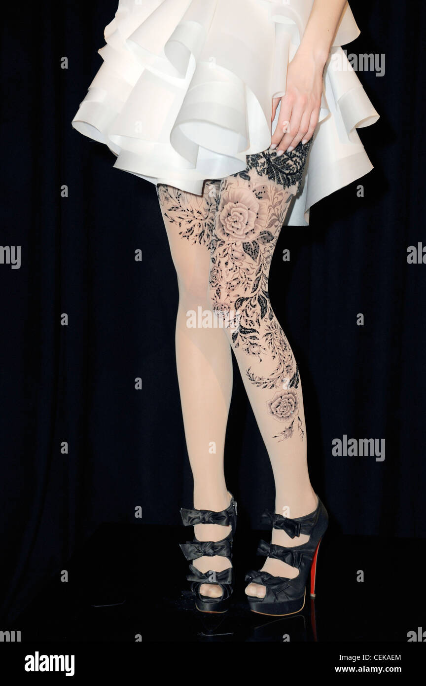 Layered white skirt with floral pattern tights and black platform peep tow shoes with bow detail - Stock Image
