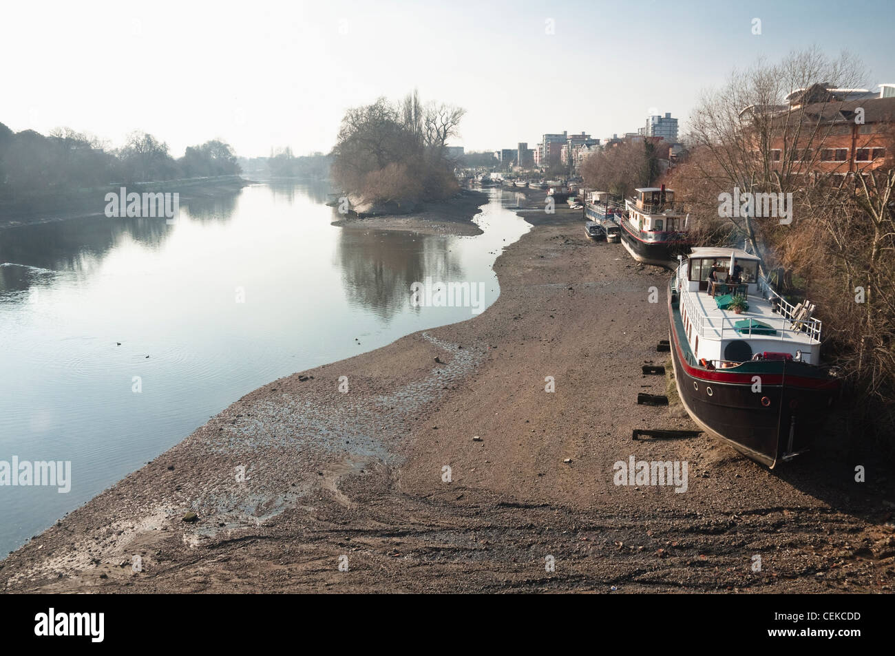 Winter low tide on the River Thames, London, with house boats on the Brentford bank. Viewed from Kew Bridge looking Stock Photo