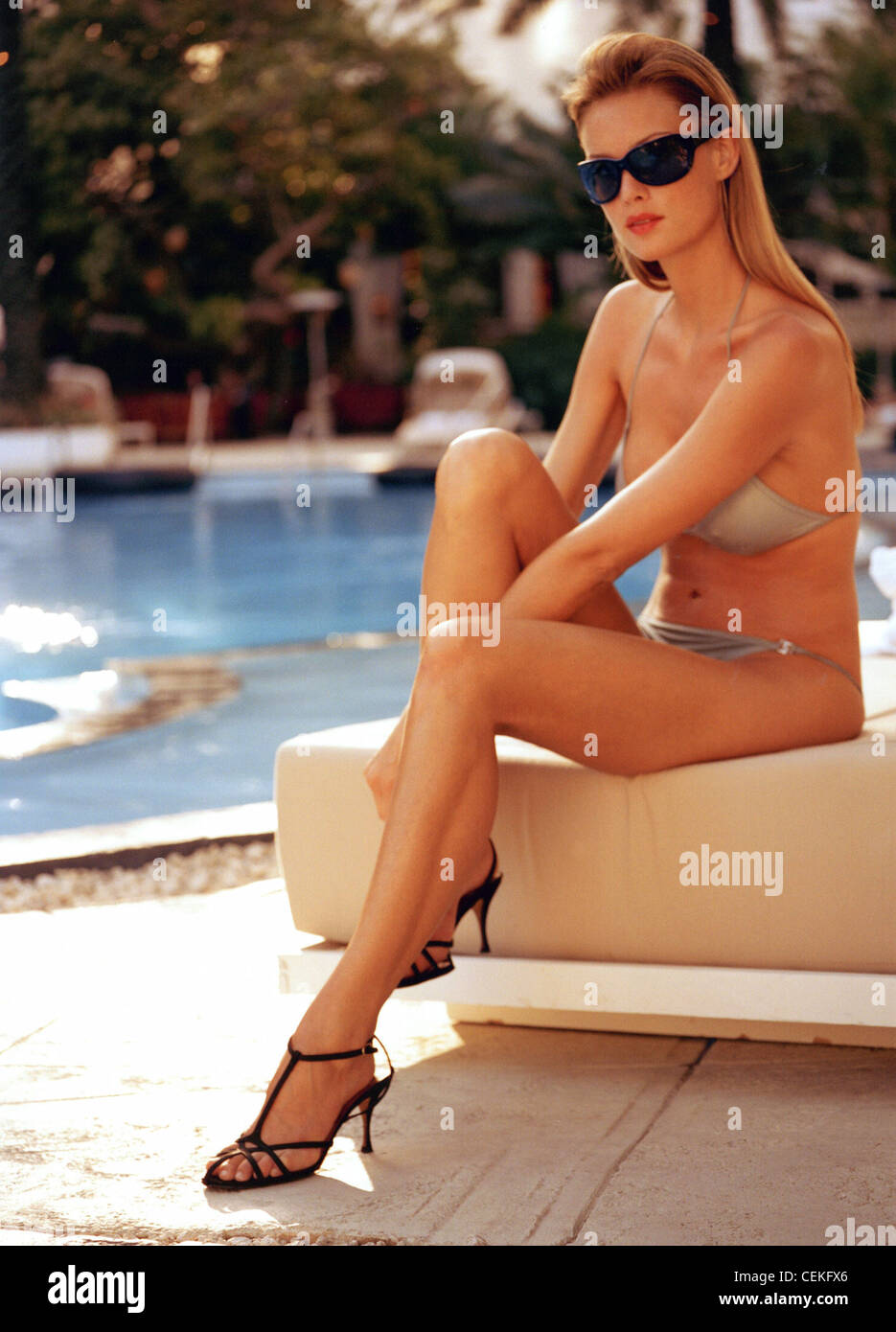 Female dark blonde straight hair worn tucked behind her ears wearing a silver bikini and strappy black high heeled - Stock Image