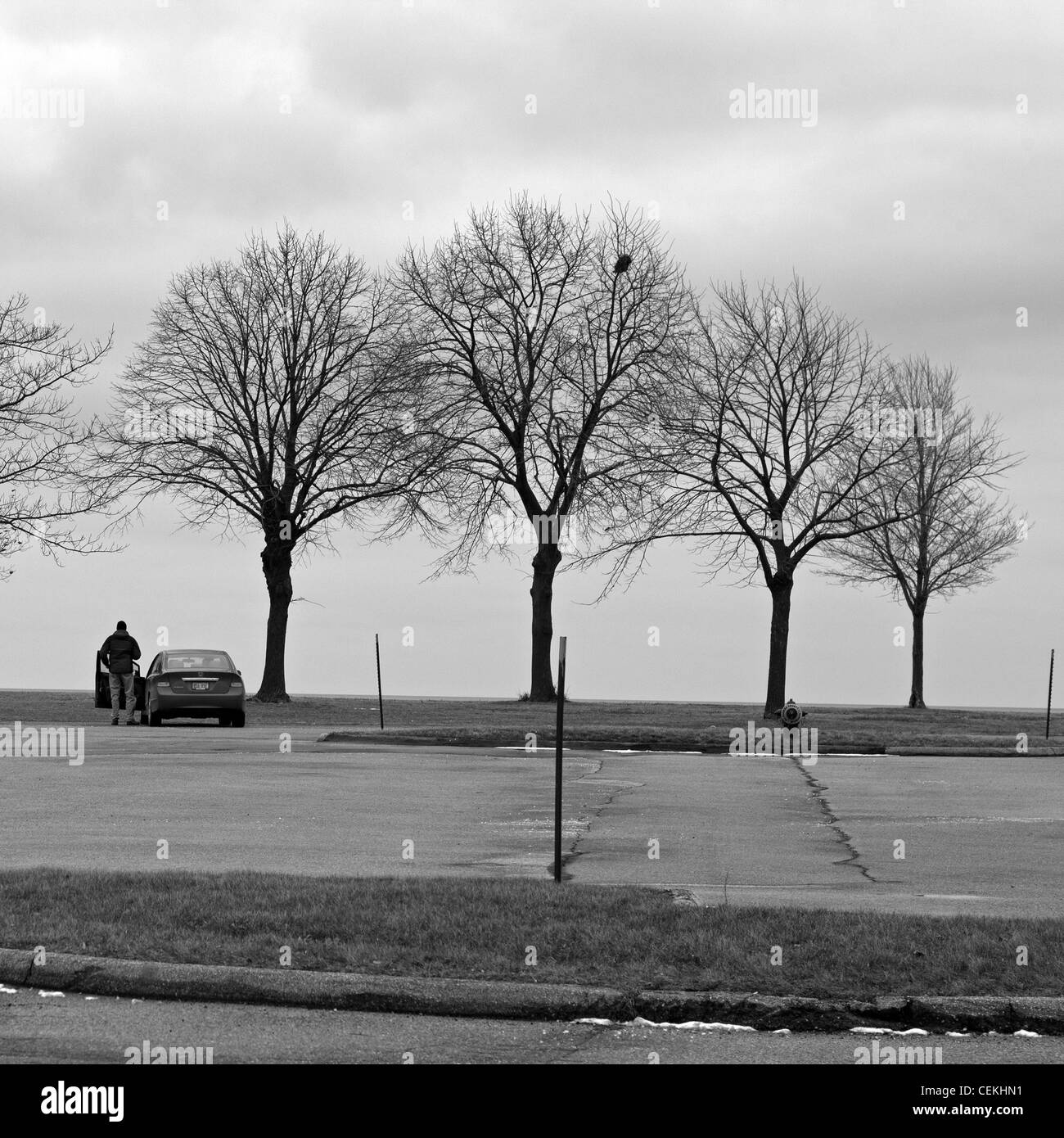 A man and his car are the only signs of life at Milwaukee's lakefront on an overcast afternoon. - Stock Image