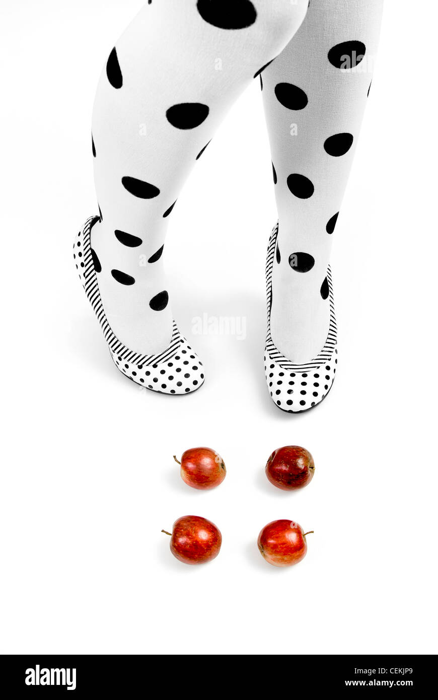 legs, dotted tights and shoes, and red apples. metaphorical: diet and shape - Stock Image