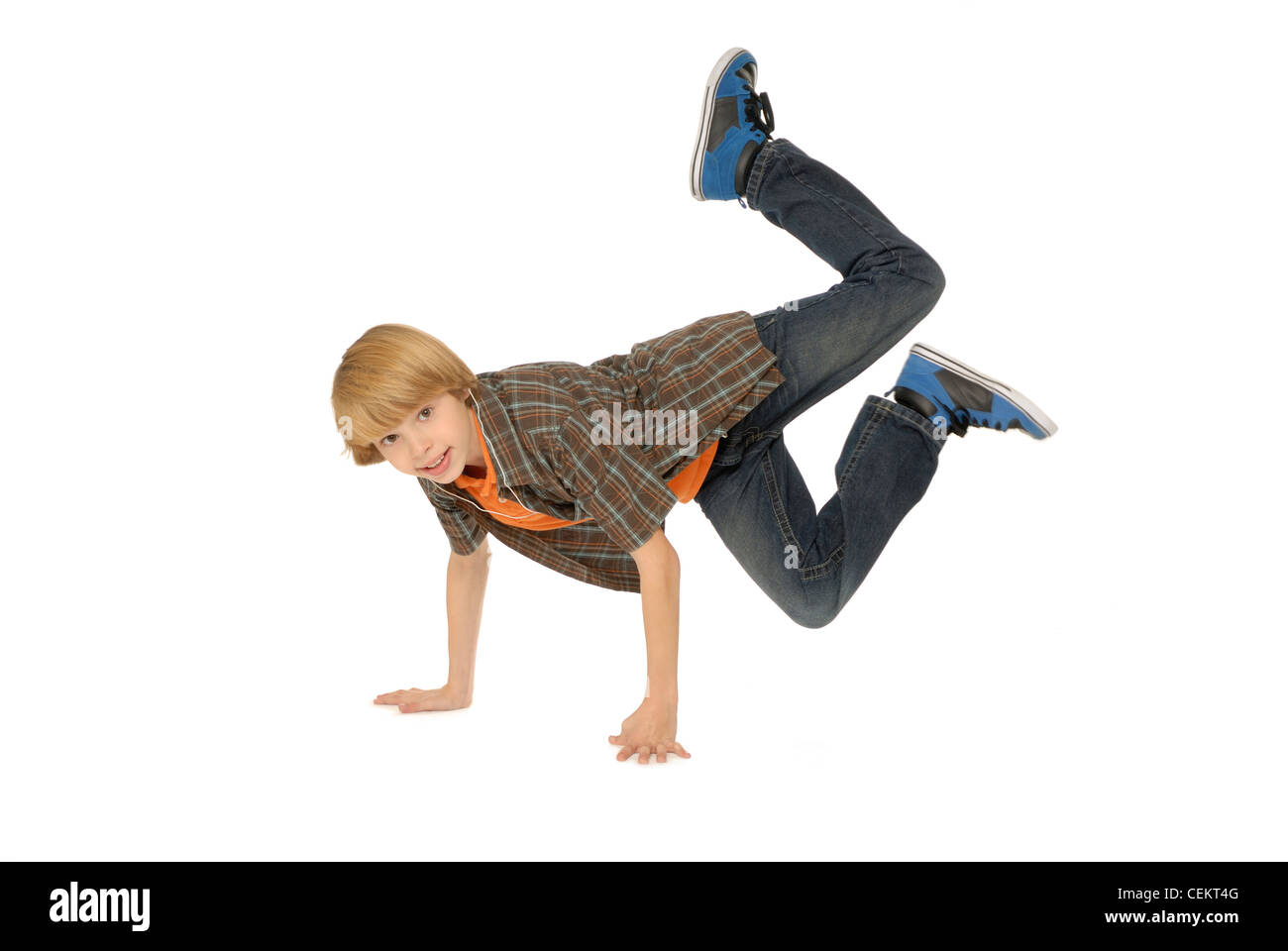 Eleven year old boy wearing earbuds, listening to mp3 player and dancing on the floor. - Stock Image