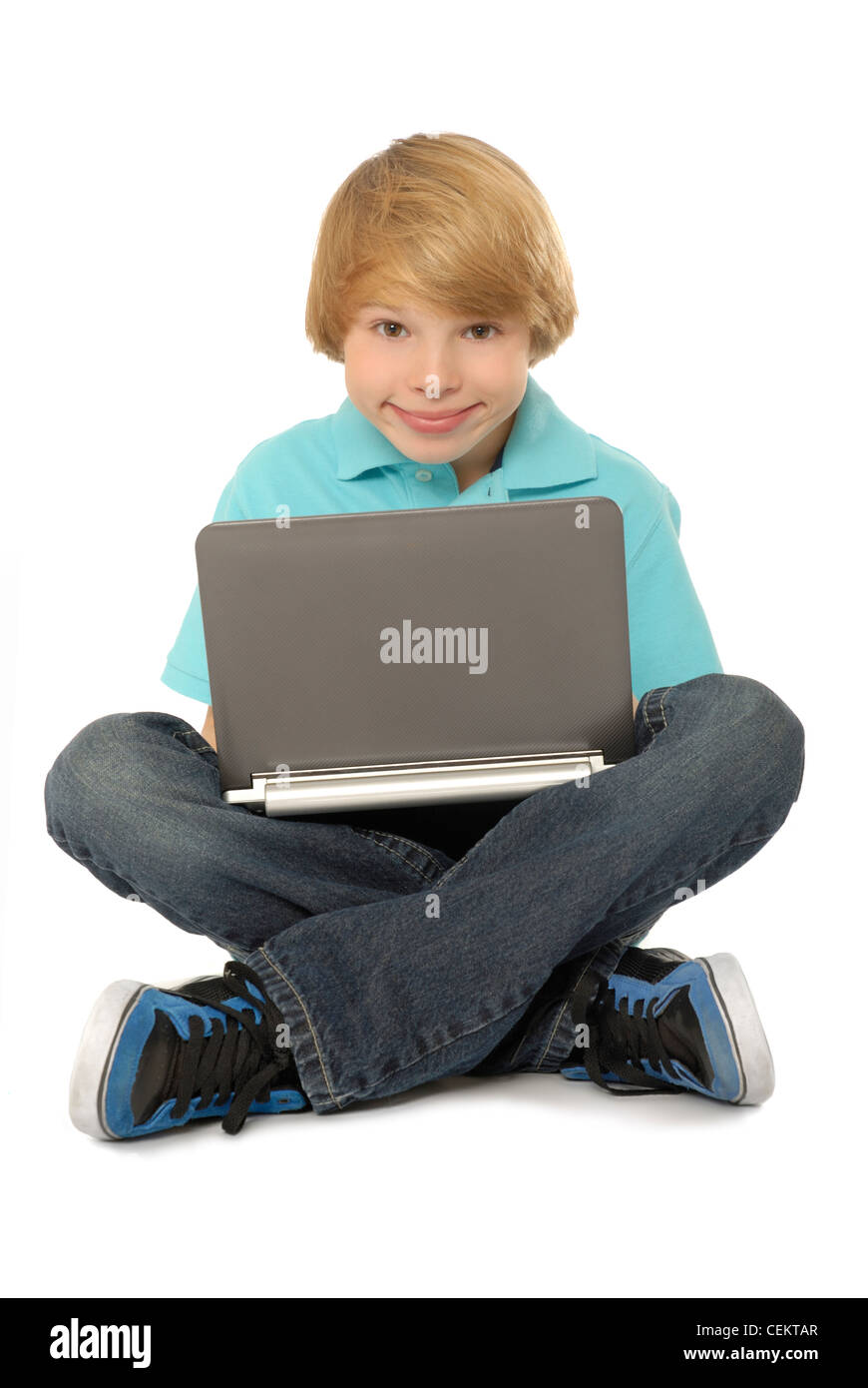 Eleven year old boy sitting and using laptop computer. - Stock Image