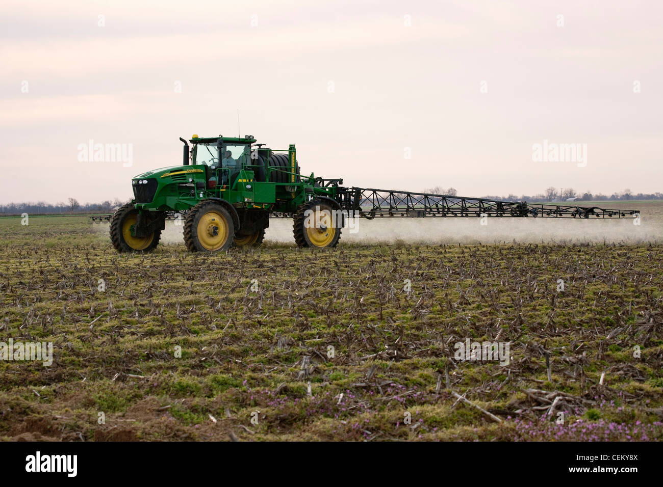 A John Deere sprayer applies pre-plant burndown herbicide in late Winter to a field that will be no-till planted - Stock Image
