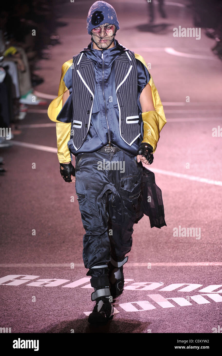 John Galliano Paris Menswear Spring Summer Model wearing baggy grey silk combat trousers, black and grey boots velcro - Stock Image