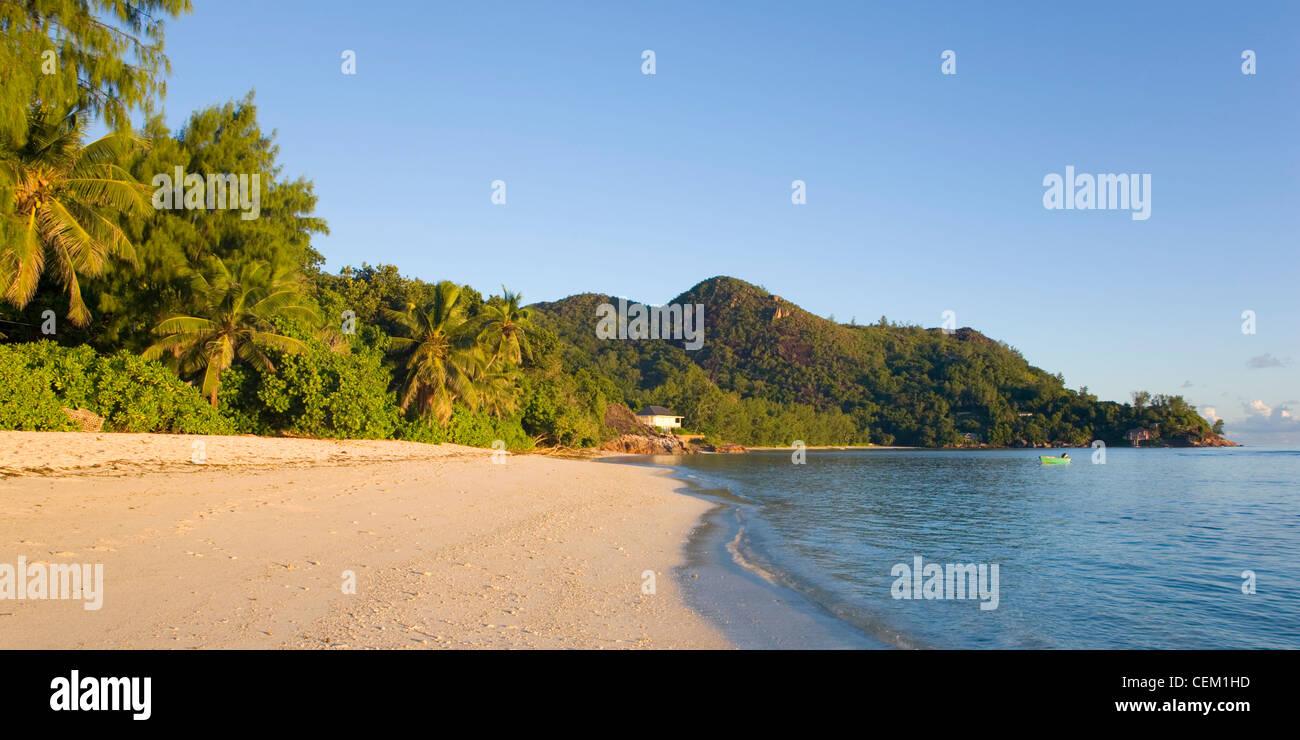 Anse La Blague, Praslin, Seychelles. View along the beach, early morning. - Stock Image