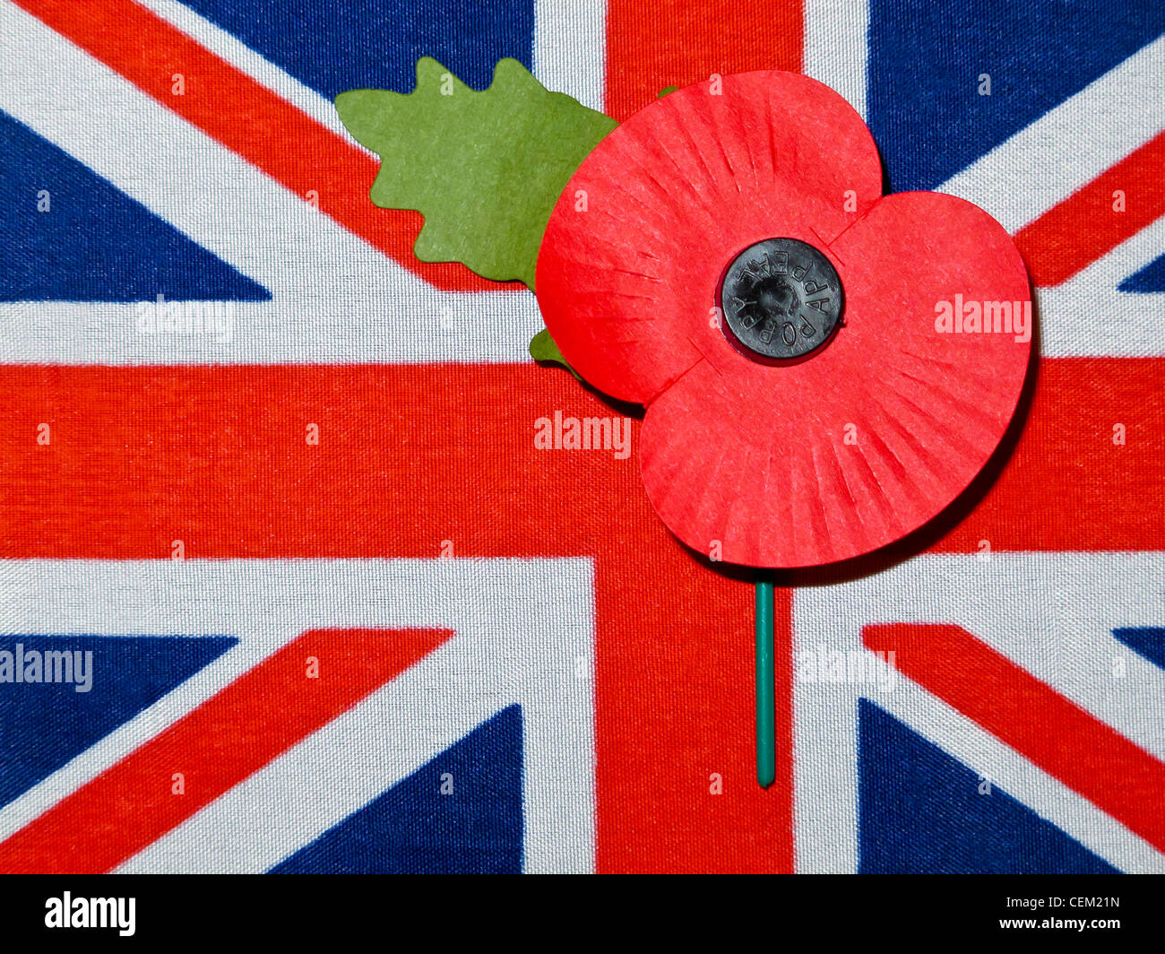 A small Union Jack flag with a rememberance poppy - Stock Image