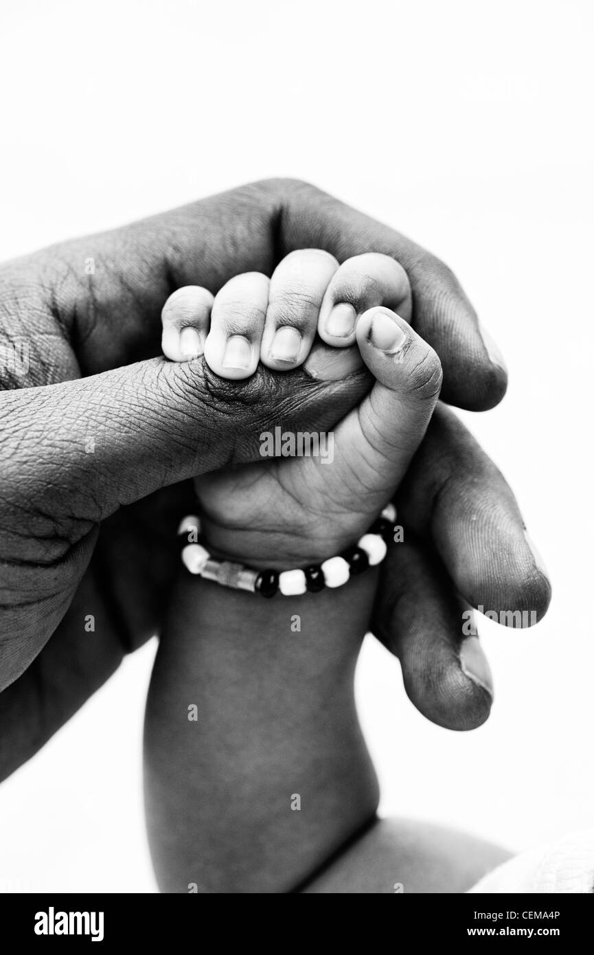 Indian mans hand holding his new born babies hand white background. Monochrome. Andhra Pradesh, India - Stock Image