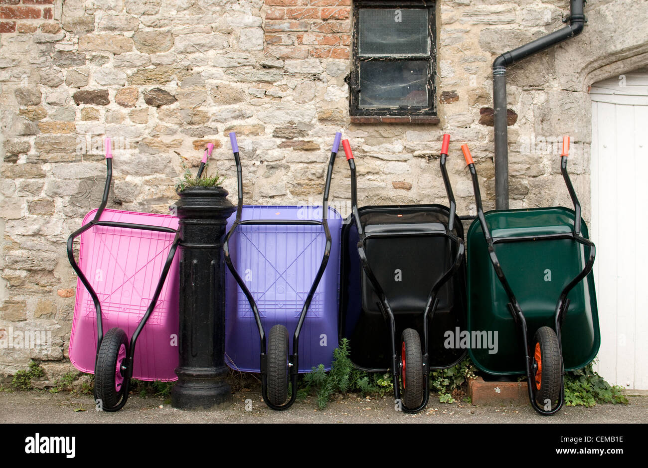 A row of colourful wheelbarrows for sale - Stock Image