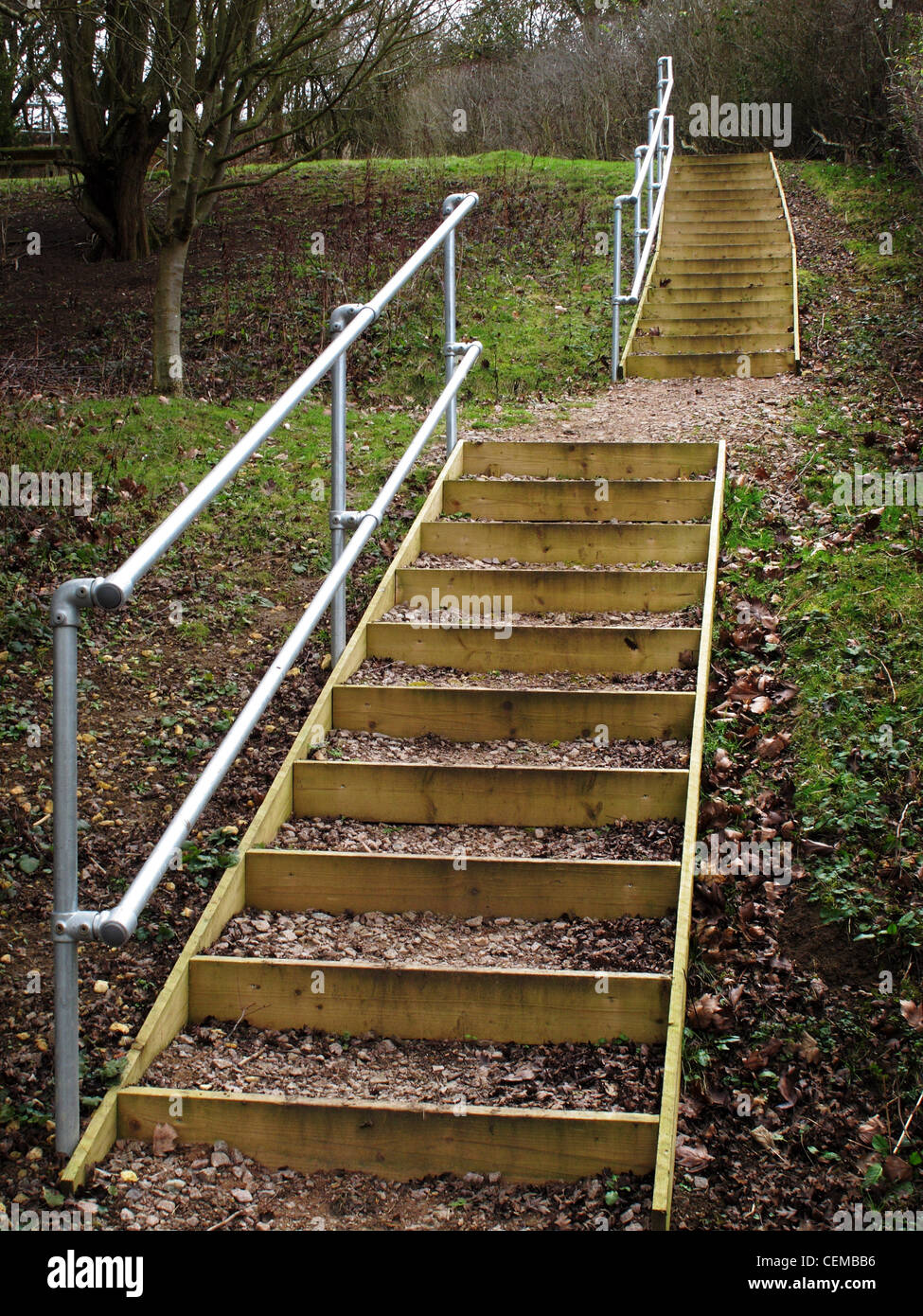 A staircase on a pathway out in the countryside, with a handrail for the safety of walkers - Stock Image