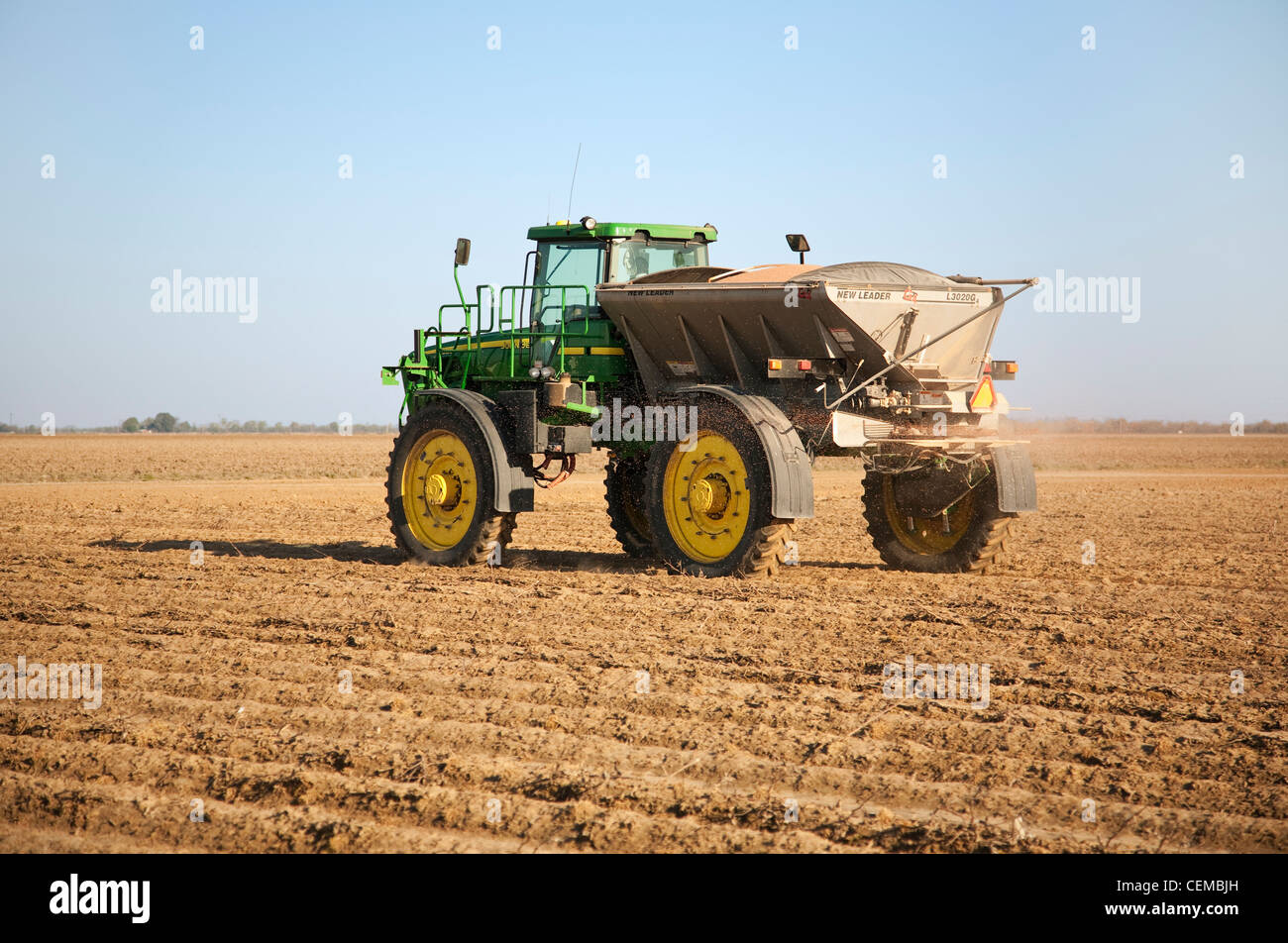A John Deere 4920 with a New Leader spreader applies dry fertilizer containing Phosphorus and Potassium to a bedded - Stock Image