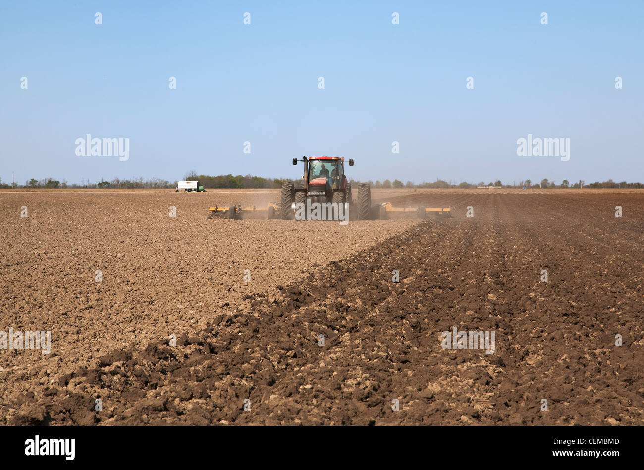 A Case IH tractor and field implement prepare bedded soil in a field in late Spring for the planting of corn / Arkansas, - Stock Image