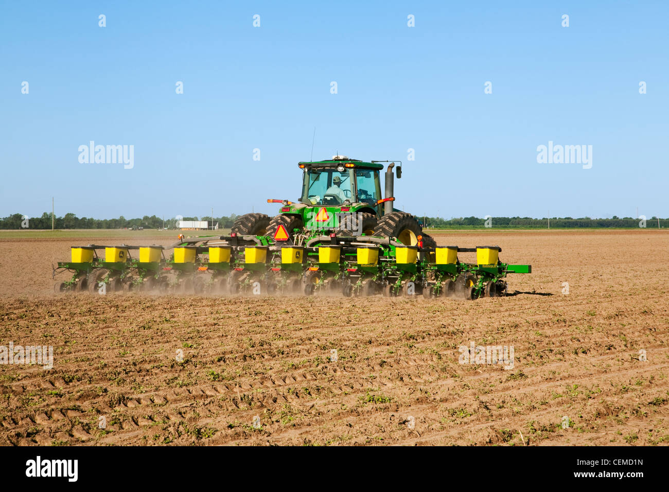 agriculture a john deere tractor and 12 row maxemerge planter plant cotton on a bedded field in mid spring arkansas usa