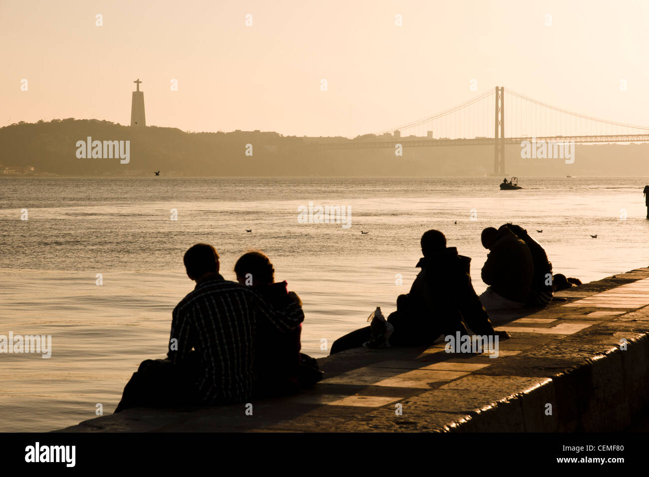 People at the Tagus riverbank at sunset. Lisbon, Portugal. - Stock Image