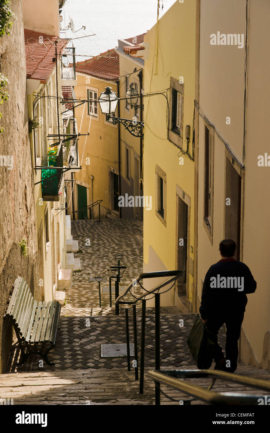 A man walks down the steps in a narrow alley in Alfama, Lisbon, Portugal. - Stock Image