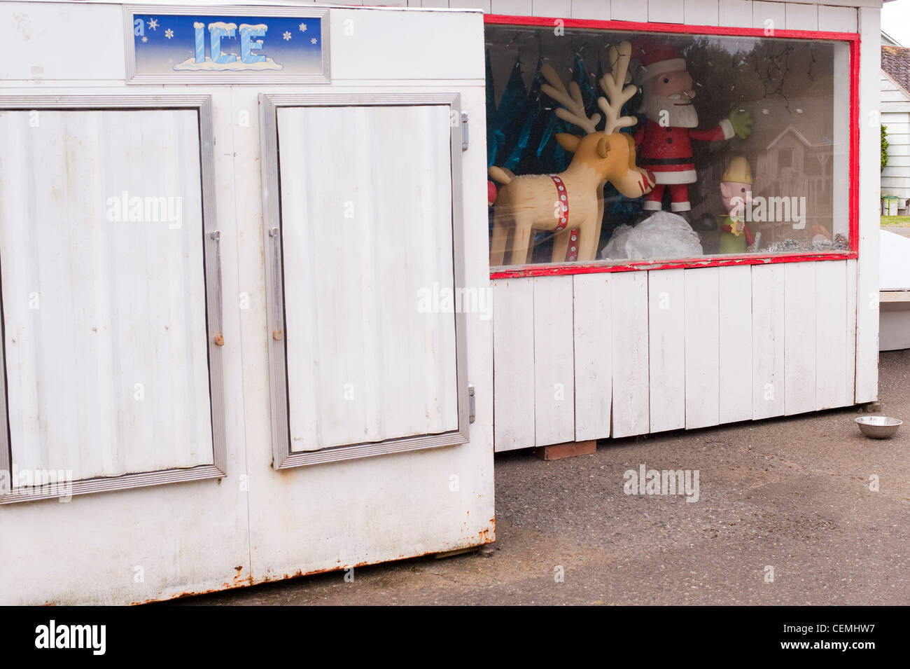 Store front with ice machine and Santa and his reindeer behind glass - Stock Image
