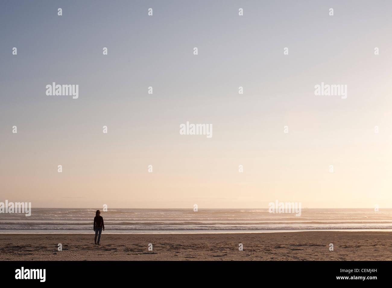Woman walking along ocean beach alone in tranquil scene - Stock Image